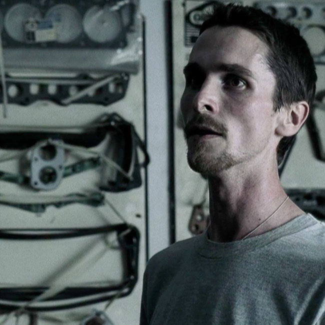A screenshot of a tired-looking actor Christian Bale in the movie The Machinist, with car parts displayed on the wall behind him.