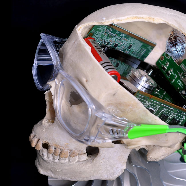 An image of a human skull with old circuit boards in its brain cavity, wearing lab safety glasses.